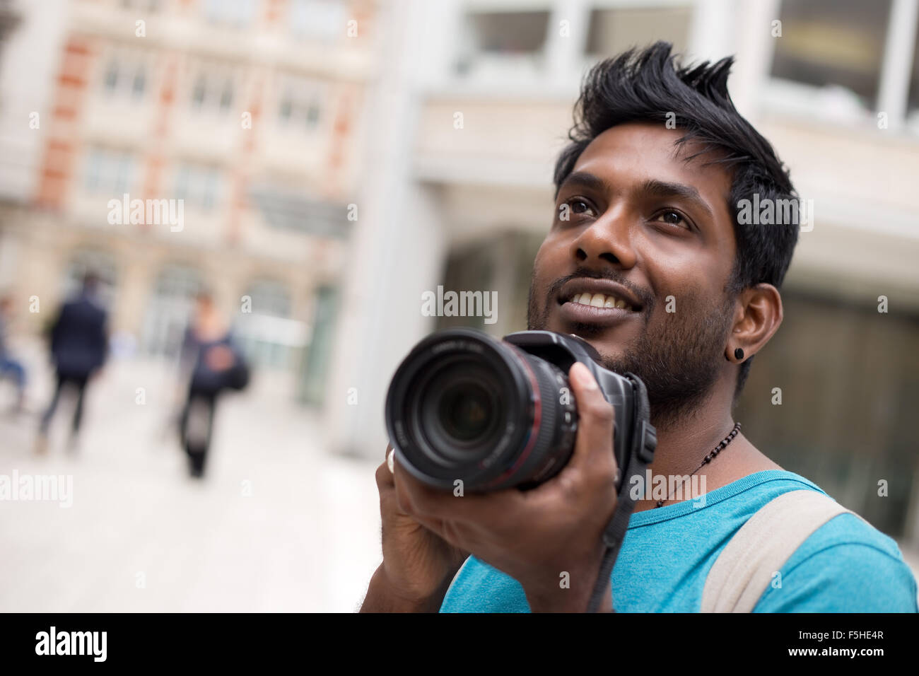 young indian man on holiday taking photos - Stock Image