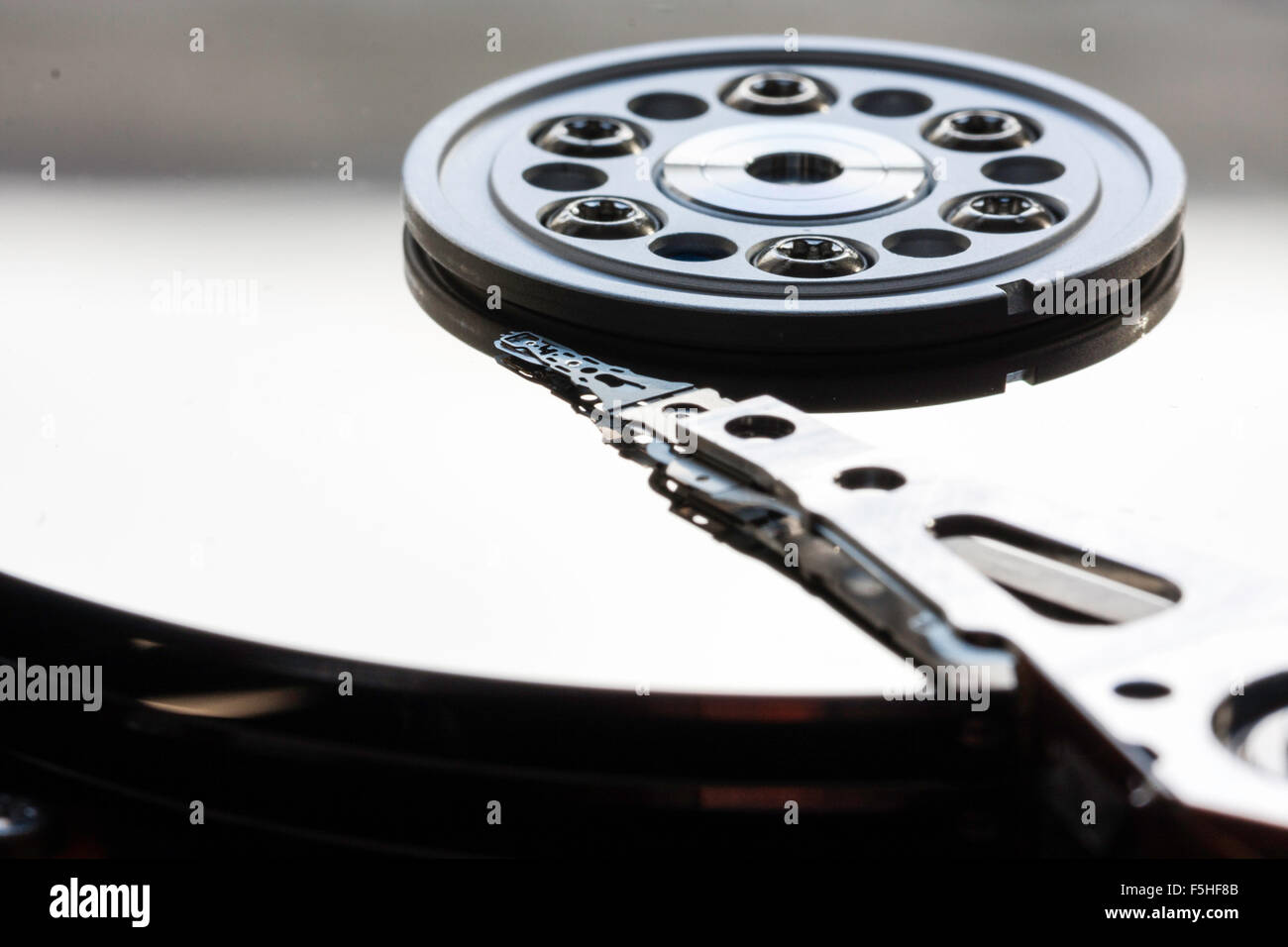 Interior of computer hard drive. Actuator arm with read and write heads over the platter and disk. Macro close up. - Stock Image