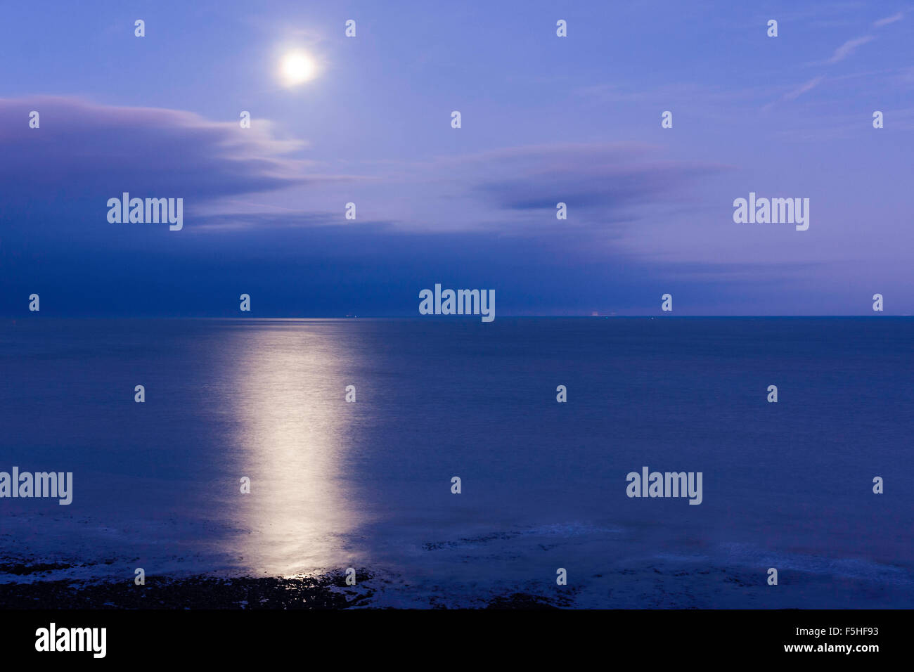 Super moon shinning in a mauve blue sky over a clam sea, the English Channel, off the kent Coast at Ramsgate, with - Stock Image