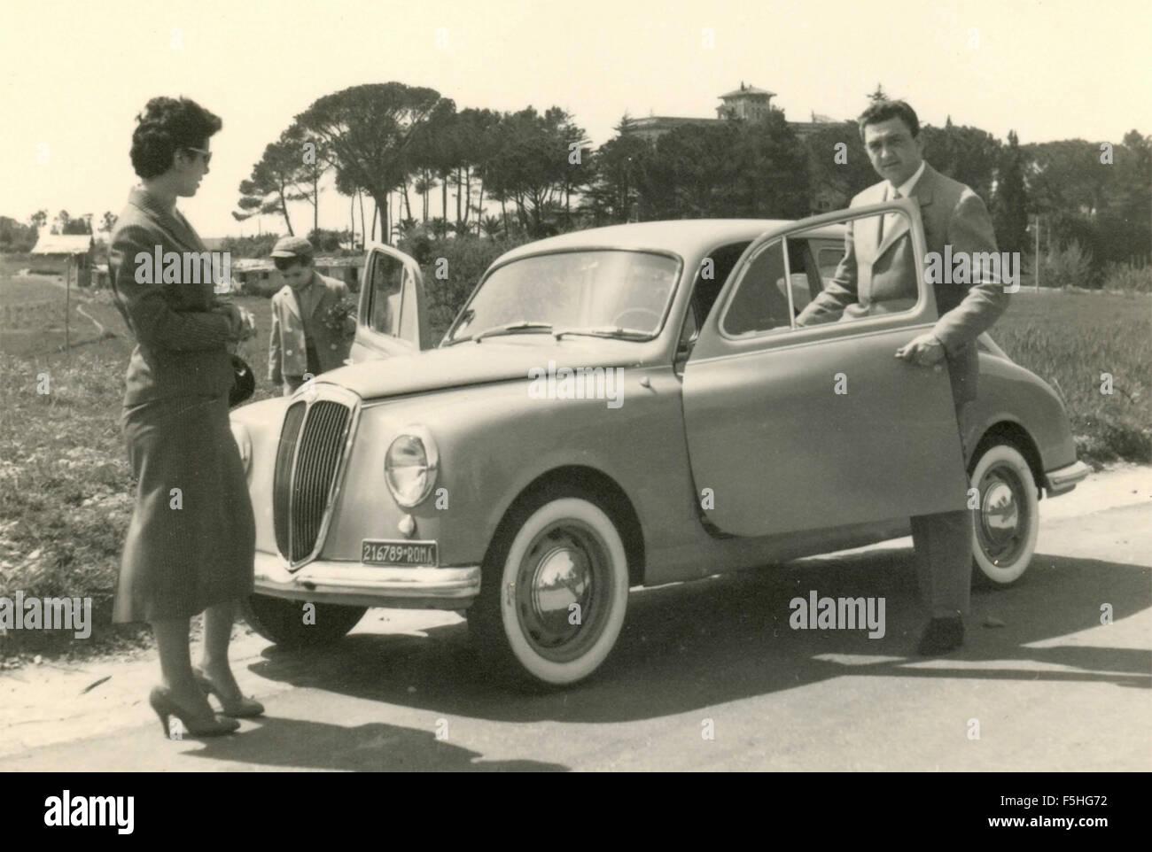 A couple next to a car Lancia Appia, Italy - Stock Image