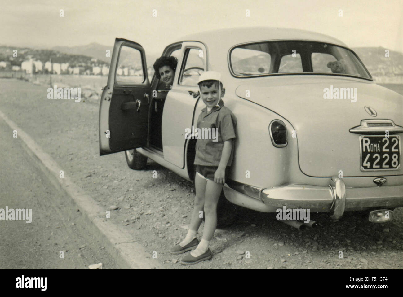 A woman and a child next to a car Lancia Appia, Italy - Stock Image
