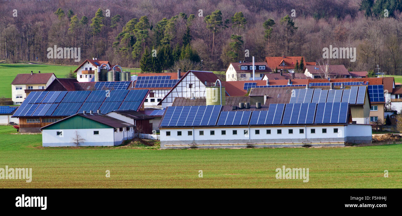 Agricultural village with modern solar cells - Stock Image