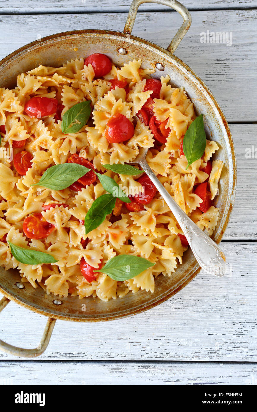 pasta with tomatoes and basil in old pan - Stock Image