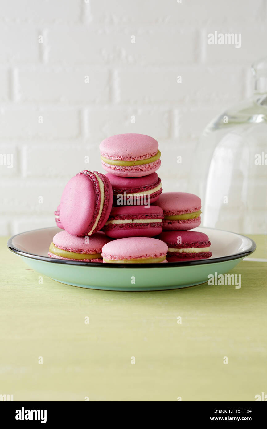 stack of fresh pink macaroons on plate - Stock Image