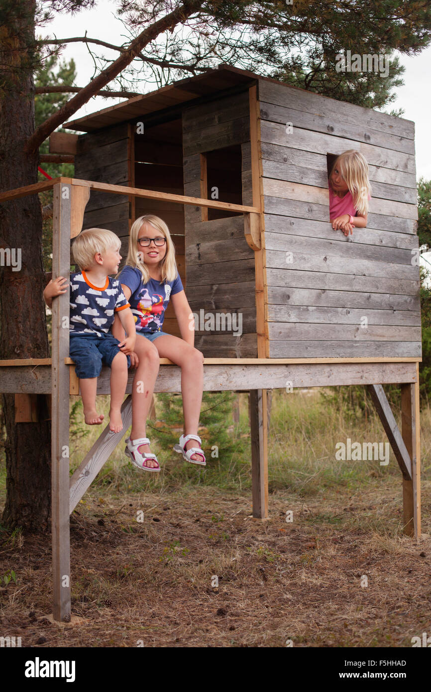 Sweden, Gotland, Faro, Boy (2-3) and sisters (8-9, 10-11) sitting on porch of tree house - Stock Image