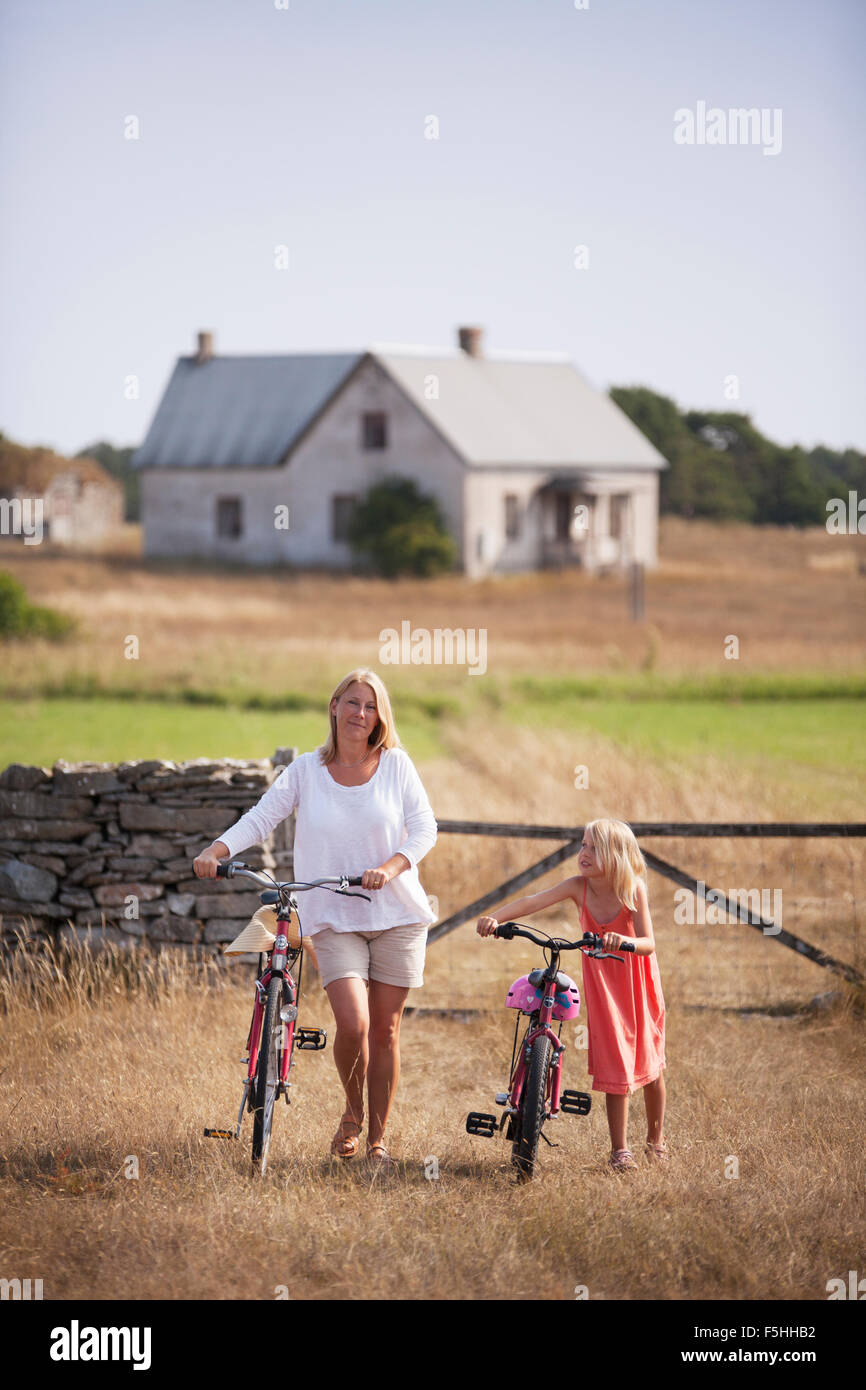 Sweden, Gotland, Faro, Mother and daughter (8-9) wheeling bicycles at farm - Stock Image