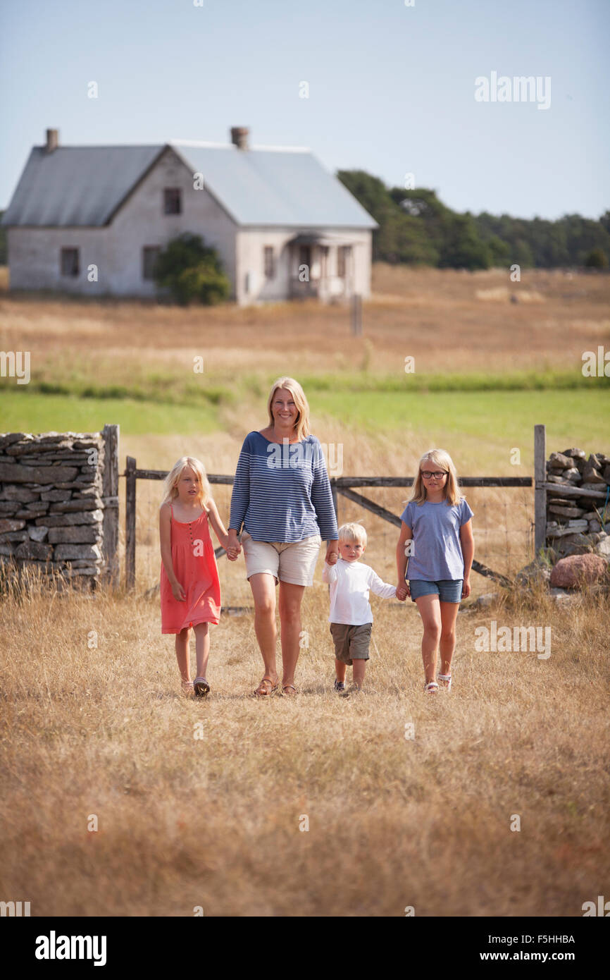 Sweden, Gotland, Faro, Mother with son (2-3) and daughters (8-9, 10-11) walking in farm yard - Stock Image