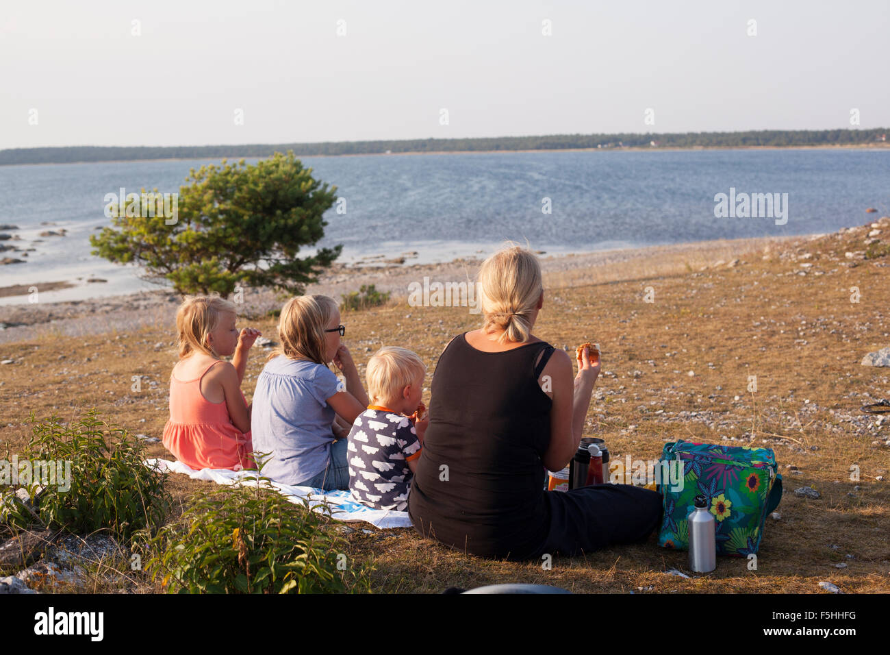 Sweden, Gotland, Faro, Gamle hamn, Family having picnic at beach - Stock Image