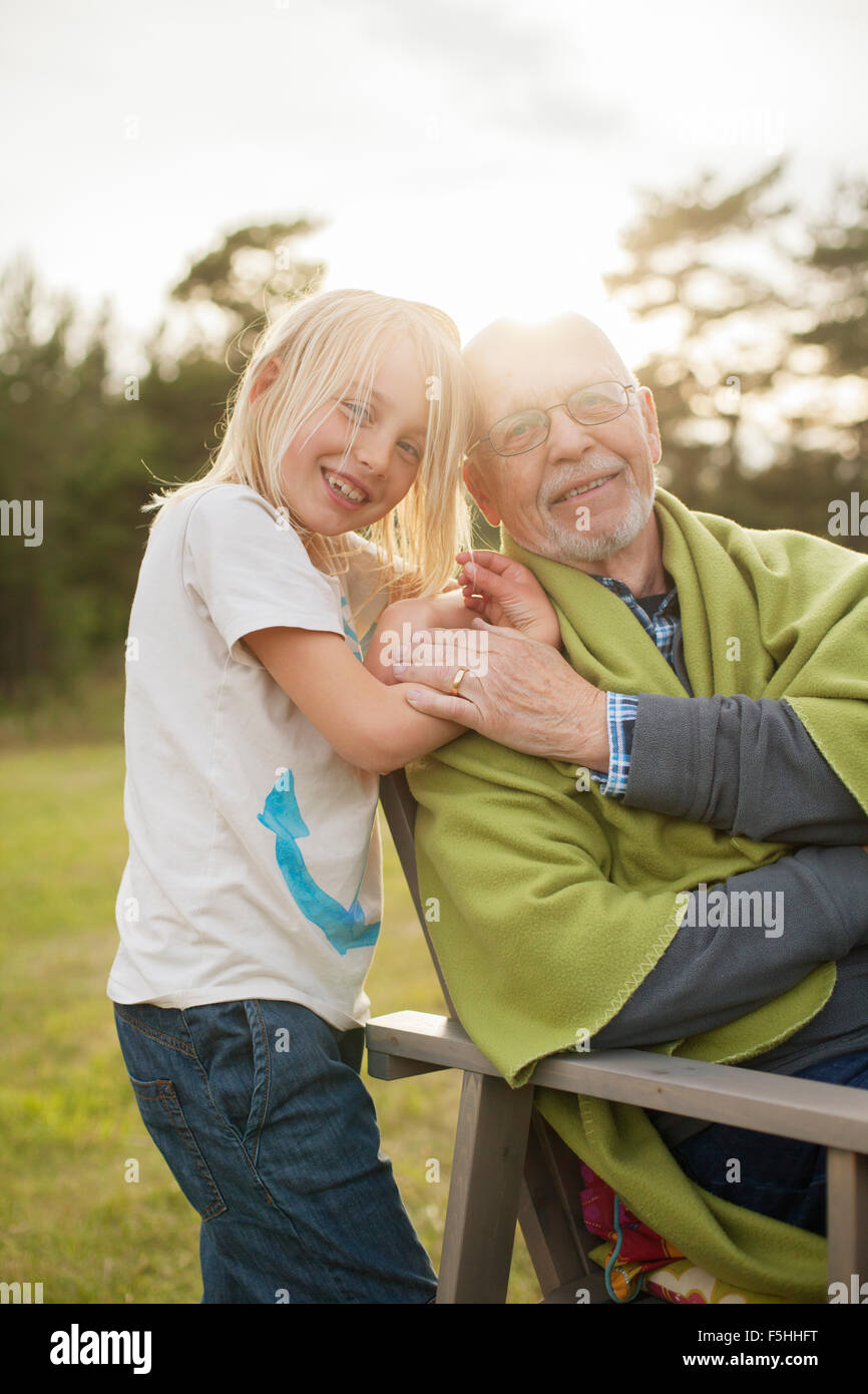 Sweden, Gotland, Faro, Portrait of grandfather with his granddaughter (8-9) in back yard - Stock Image