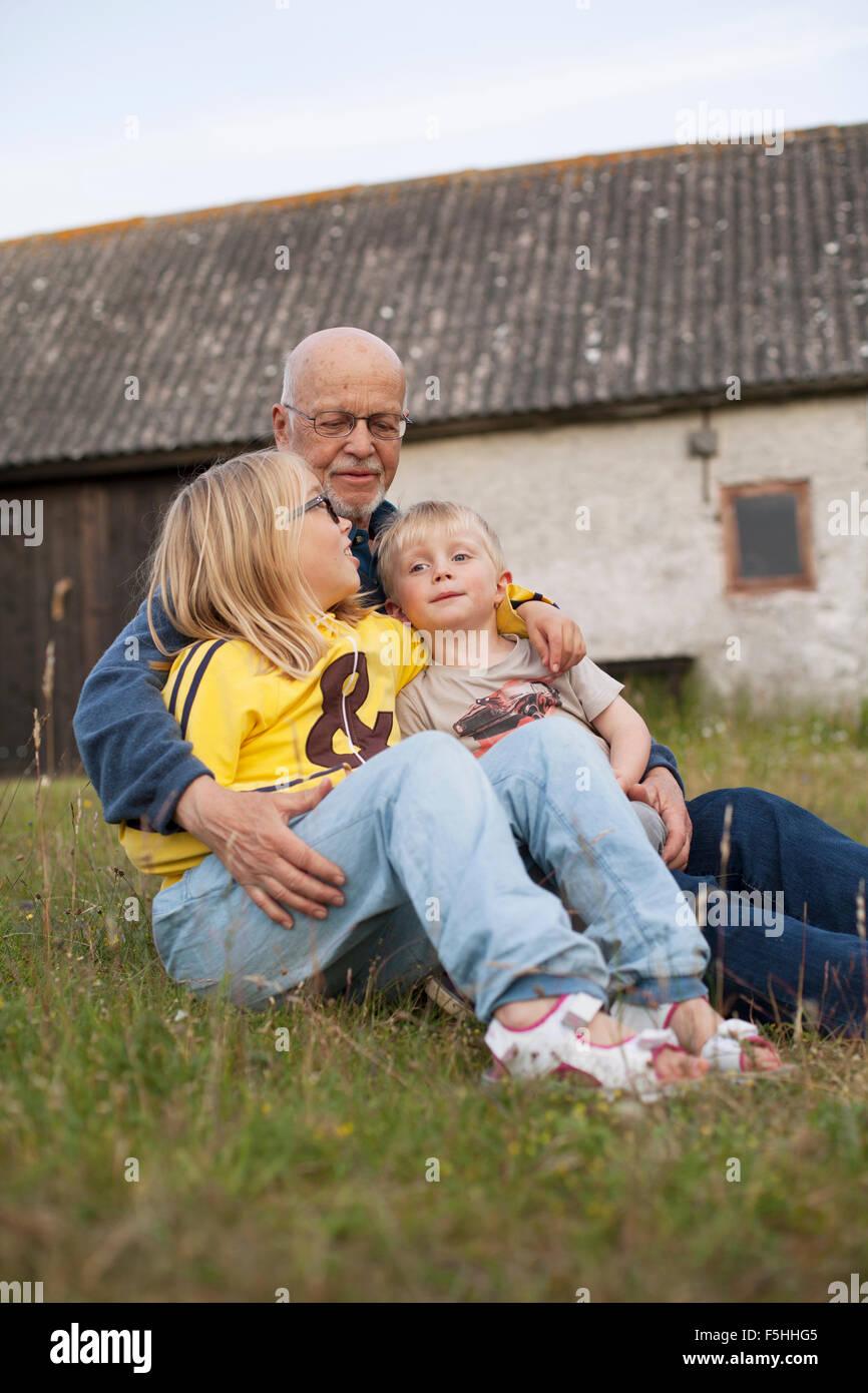 Sweden, Gotland, Faro, Grandfather talking with his grandchildren (2-3, 10-11) - Stock Image