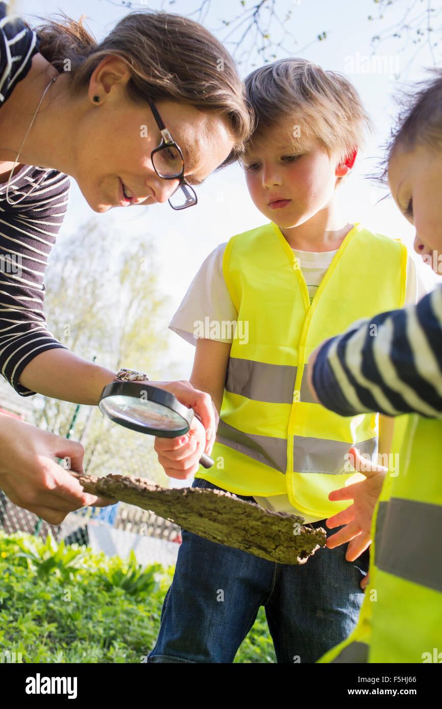 Sweden, Vastergotland, Olofstorp, Bergum, Woman taking care of children (2-3, 6-7) outdoors - Stock Image