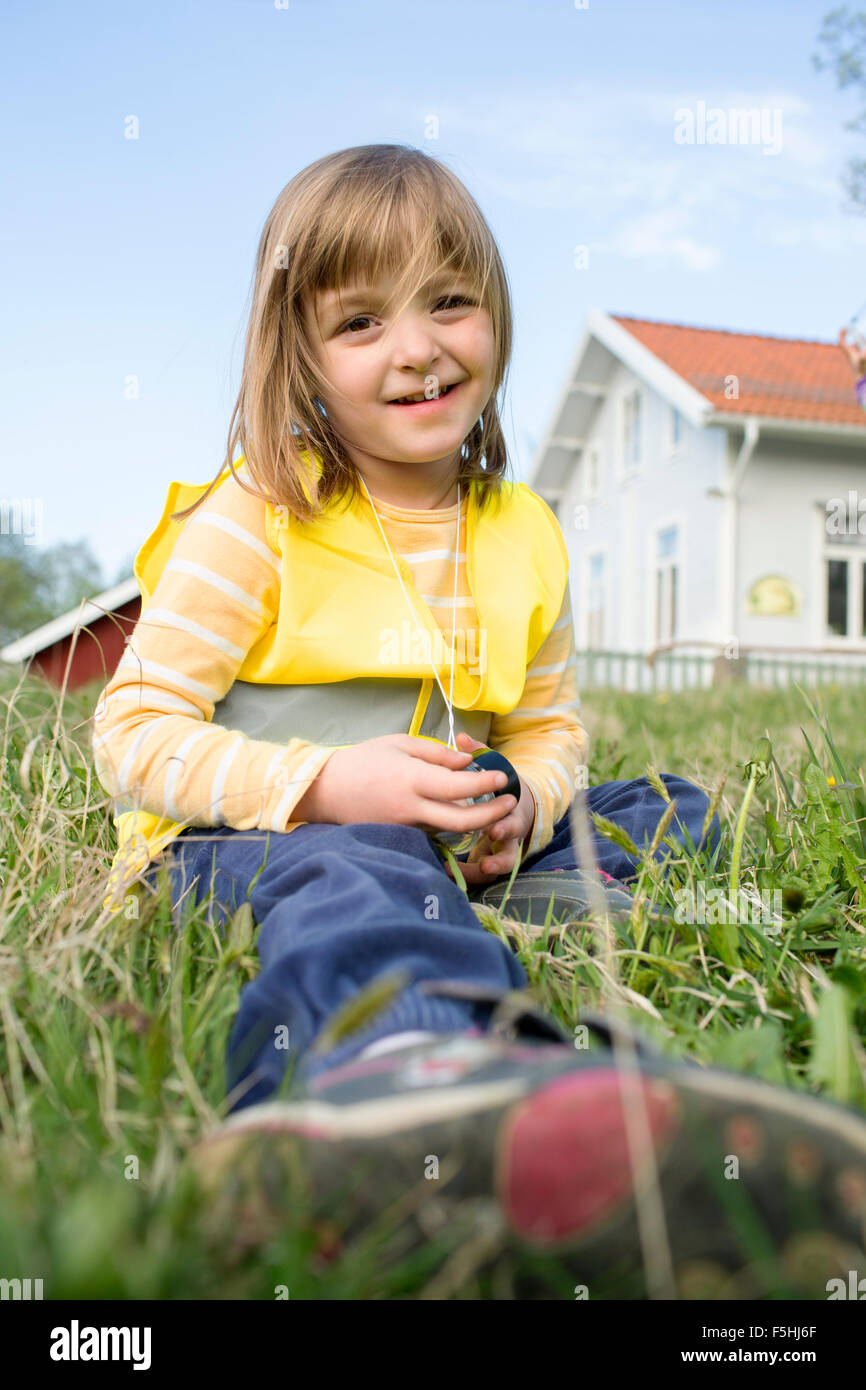 Sweden, Vastergotland, Olofstorp, Bergum, Portrait of girl (4-5) sitting in grass - Stock Image