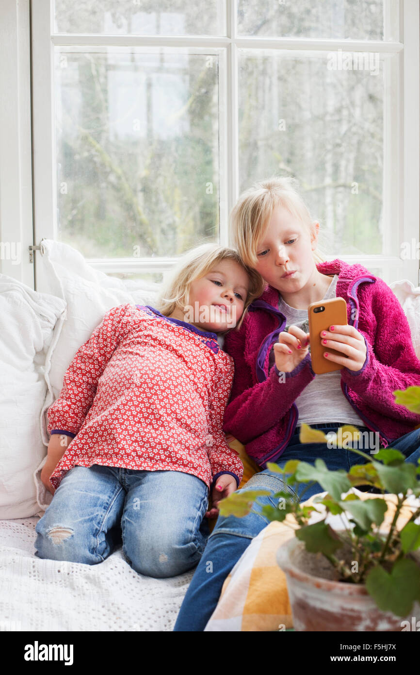 Sweden, Sisters (4-5, 10-11) using smart phone at home - Stock Image