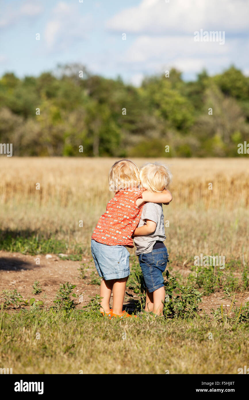 Sweden, Gotland, Havdhem, Boy and girl (2-3) hugging - Stock Image