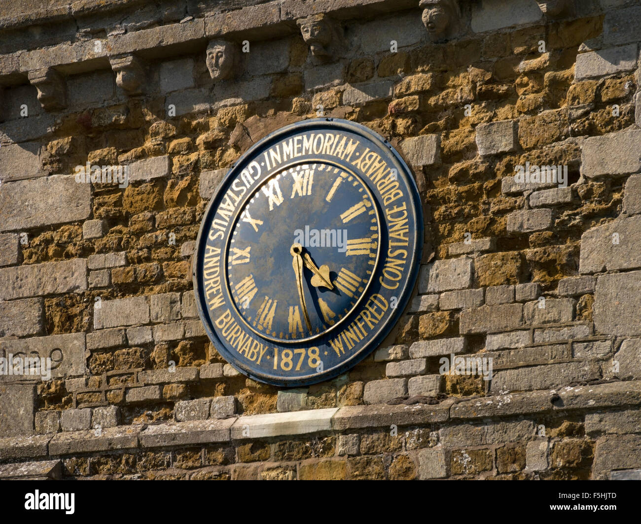 Old church clock face with gold roman numerals and memorial inscription, St. Mary's church, Burrough, Leicestershire, - Stock Image