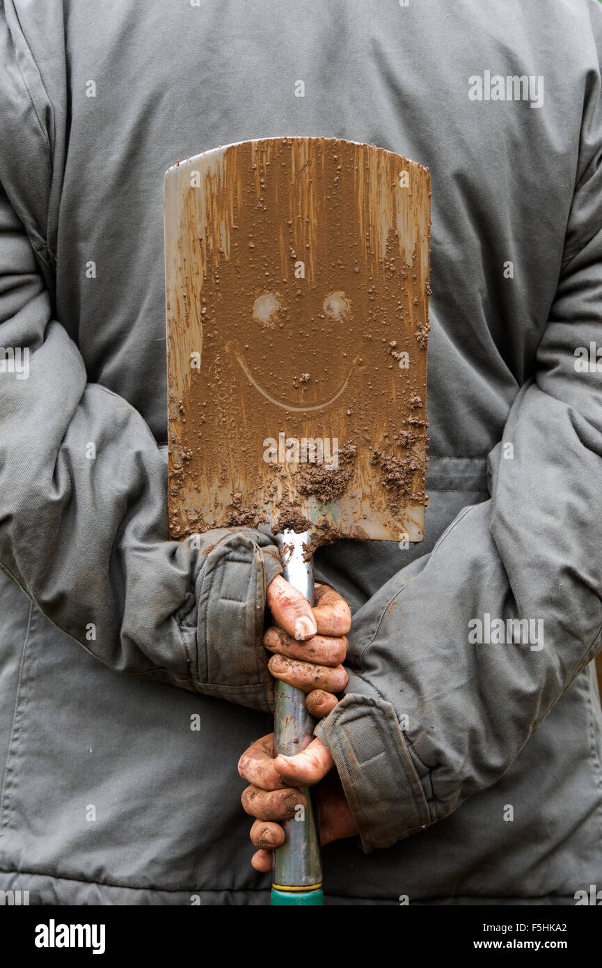 Gardener holding a smiley muddy spade - Stock Image