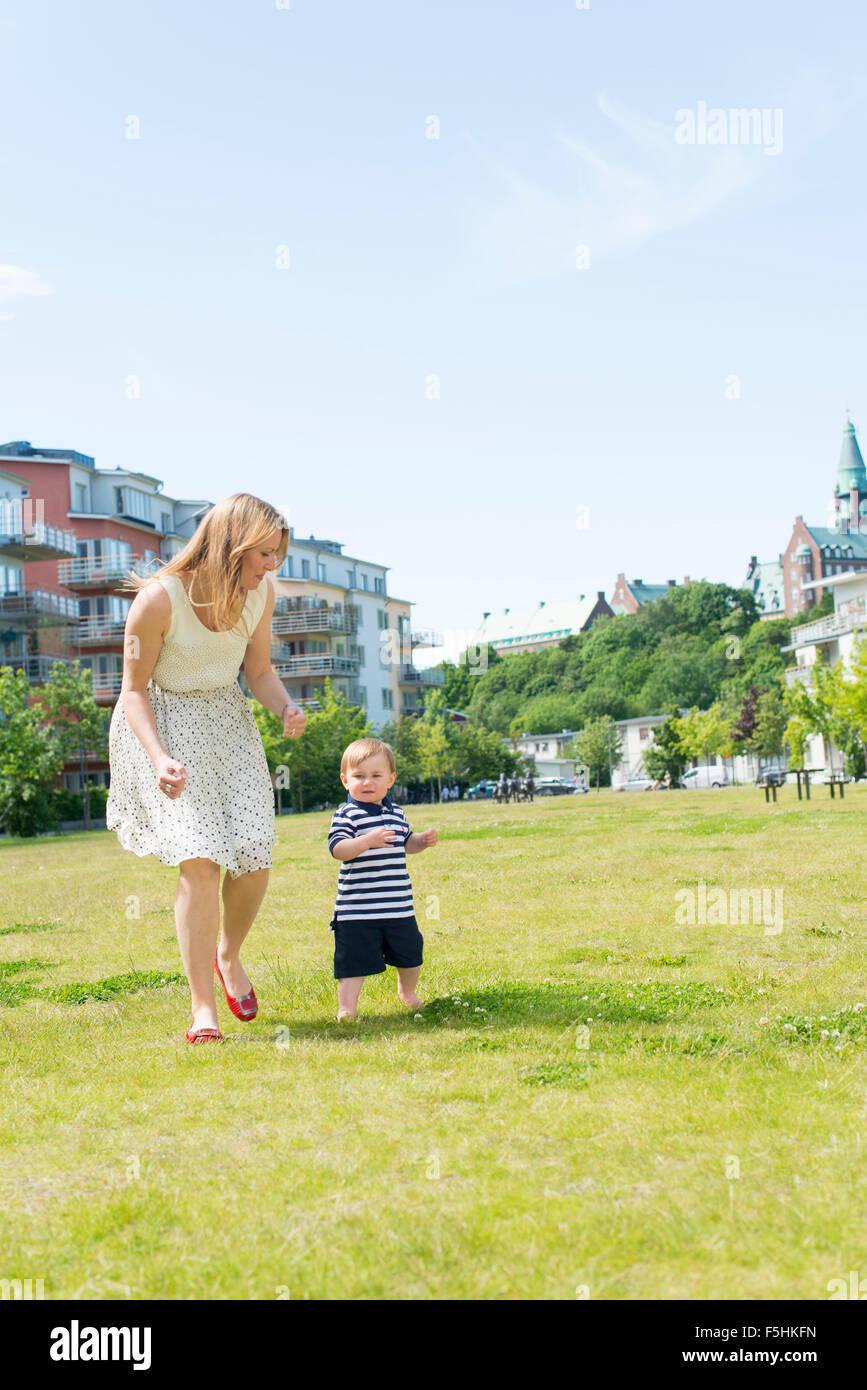 Sweden, Sodermanland, Nacka, Finnboda Hamn, Mother with baby boy (18-23 months) in park - Stock Image