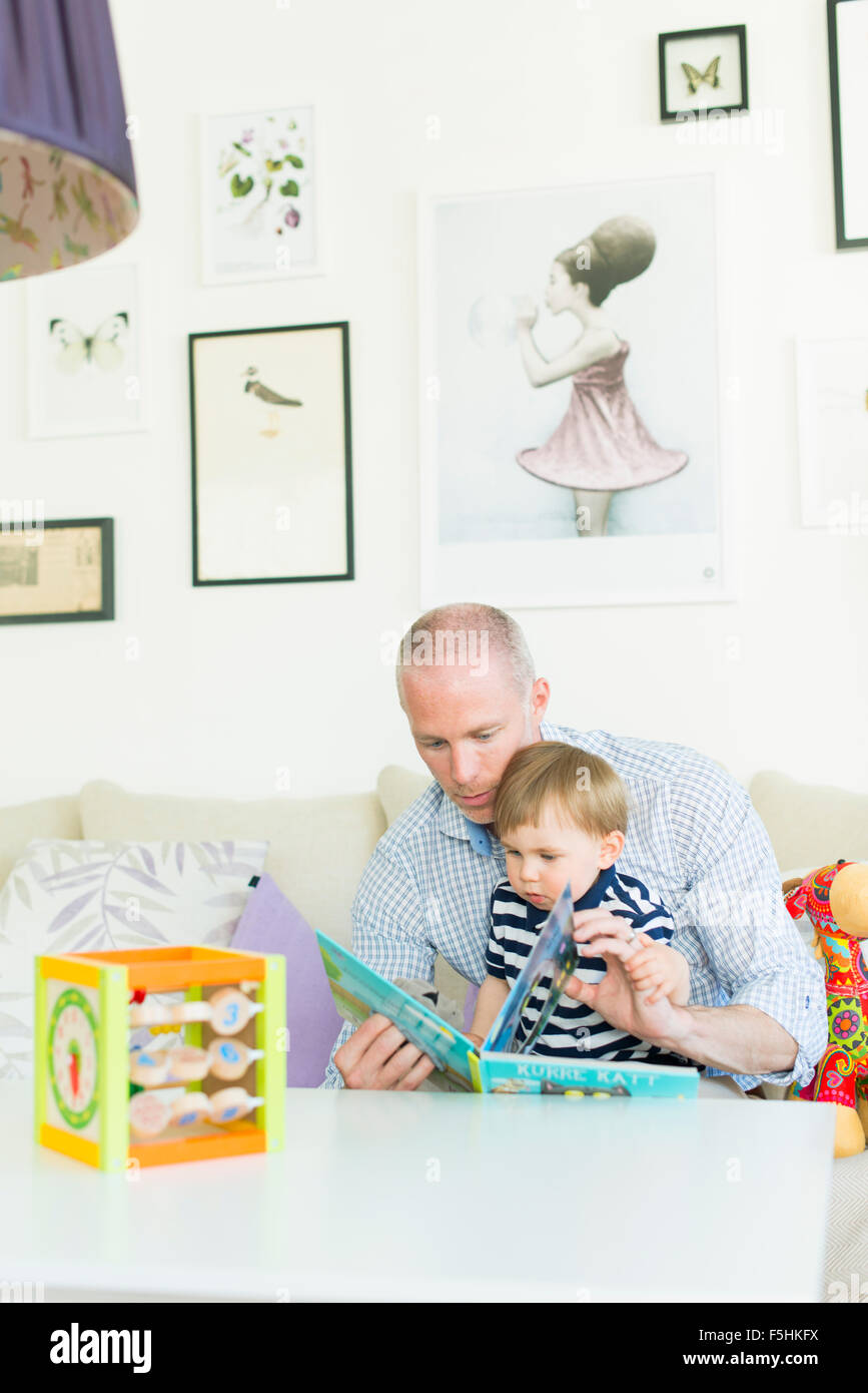 Sweden, Man reading to his son (18-23 months) - Stock Image