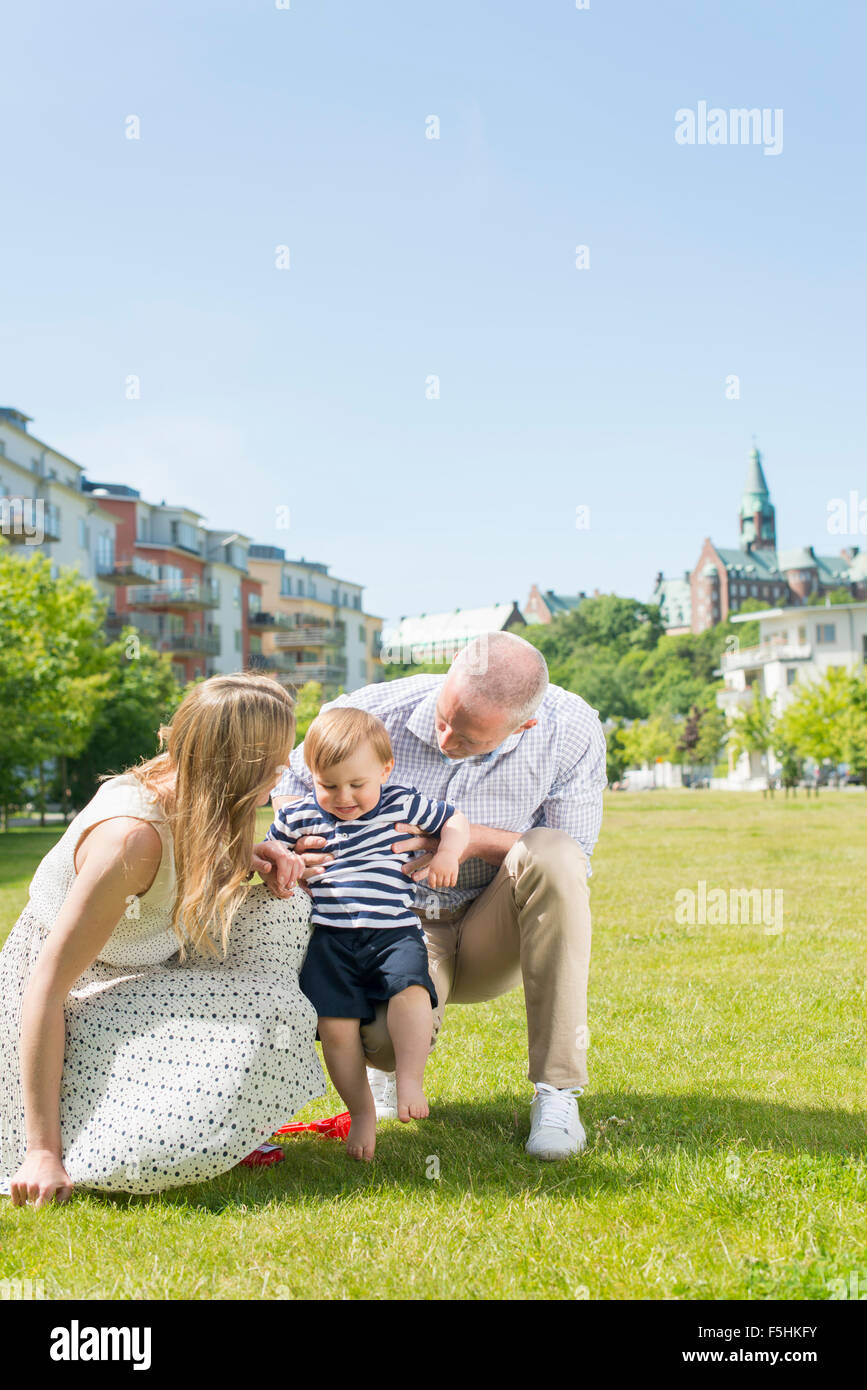 Sweden, Sodermanland, Nacka, Finnboda Hamn, Parents assisting son (18-23 months) with first steps - Stock Image