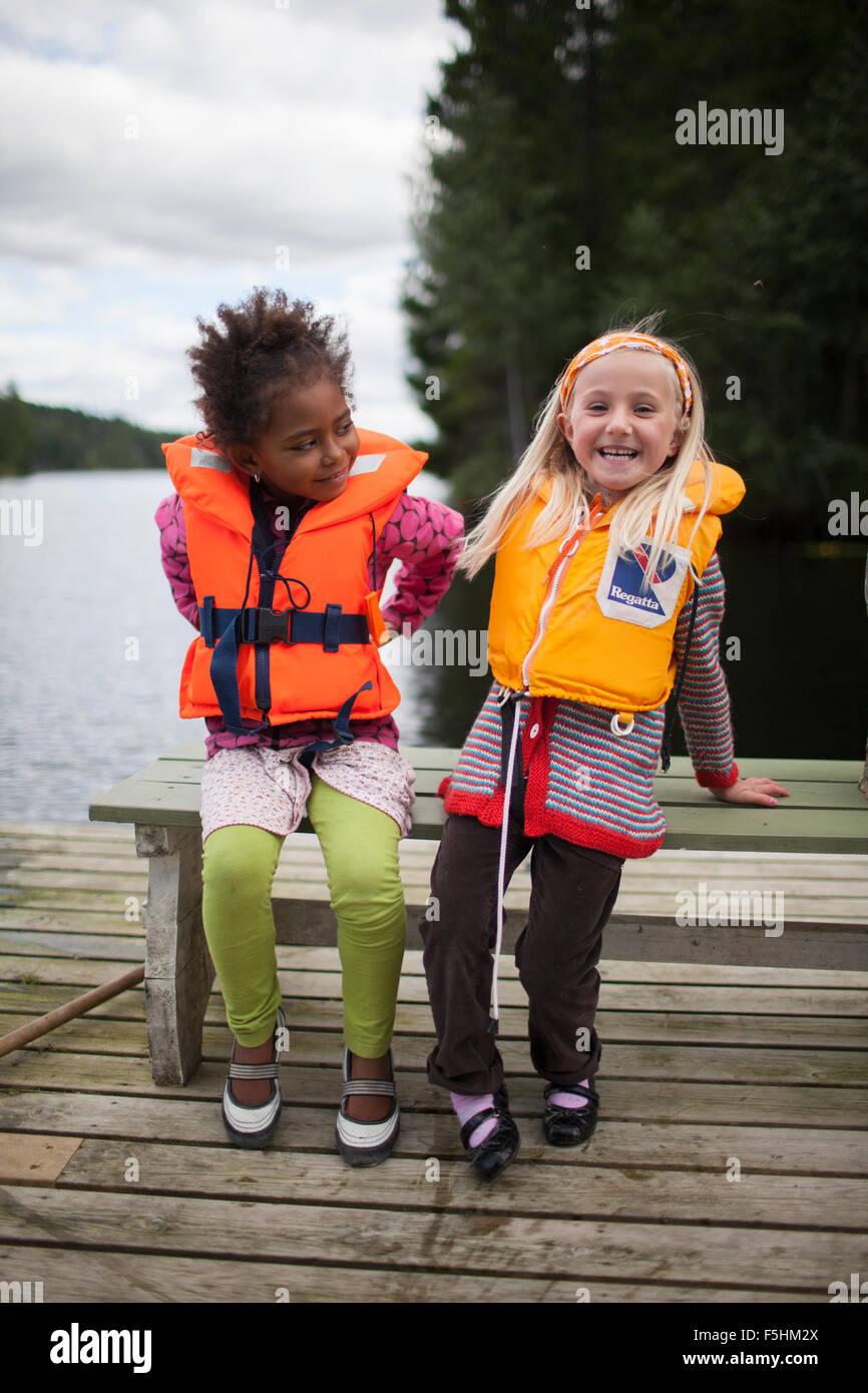 Sweden, Medelpad, Two girls (6-7) wearing life jackets - Stock Image