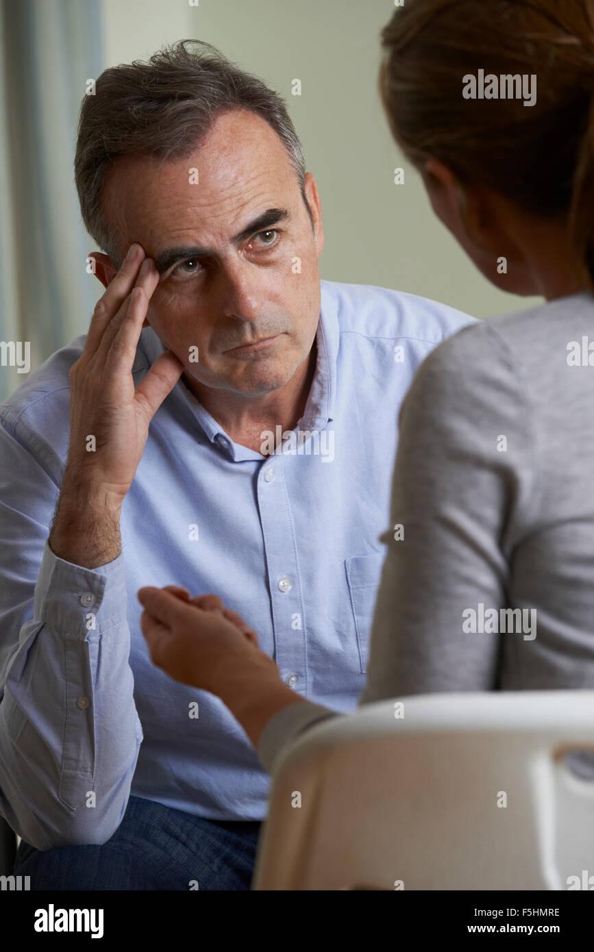Depressed Mature Man Talking To Counselor - Stock Image
