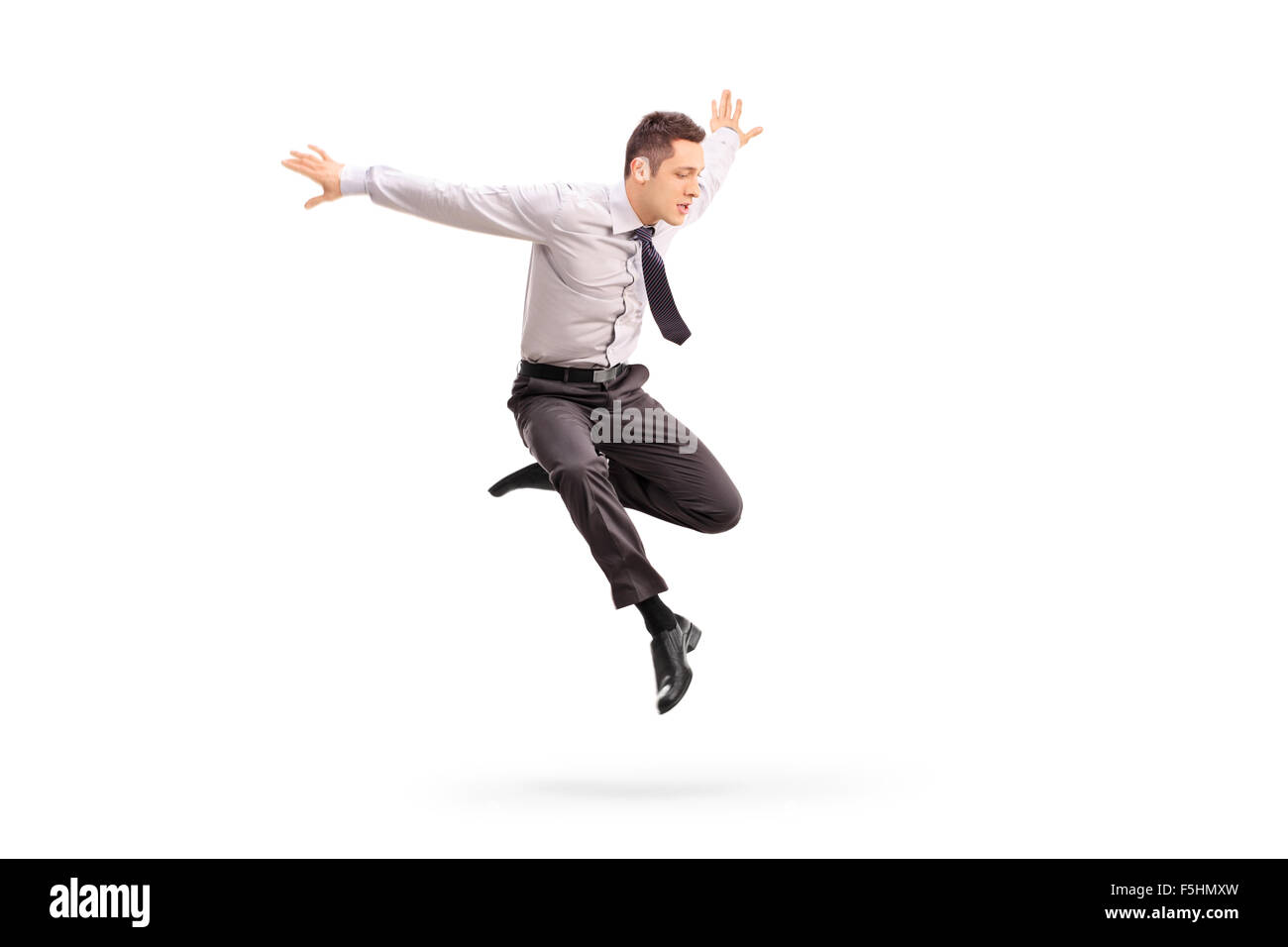 Studio shot of a young businessman jumping in the air isolated on white background - Stock Image