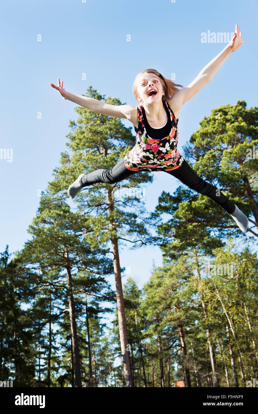 Sweden, Sodermanland, Nacka, Girl (12-13) in mid air in front of trees - Stock Image