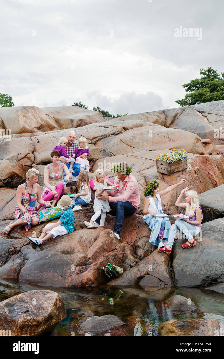 Sweden, Uppland, Roslagen, Big family having picnic on rocks at seaside - Stock Image