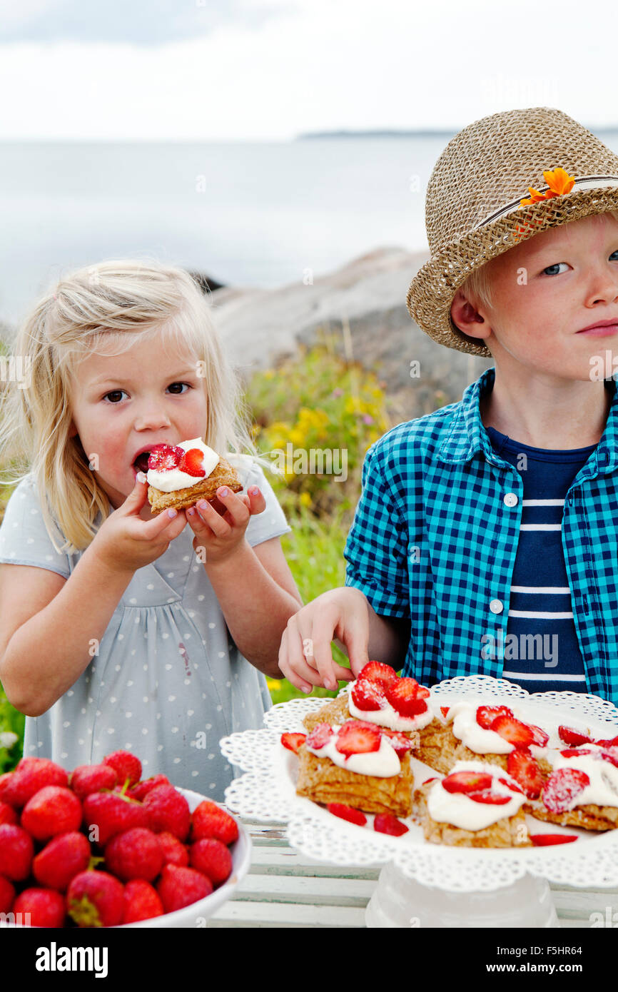 Sweden, Uppland, Roslagen, Children (6-7, 8-9) eating strawberry dessert outdoors - Stock Image