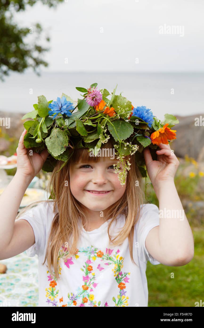 Sweden, Uppland, Roslagen, Portrait of girl (8-9) with wreath on her head - Stock Image
