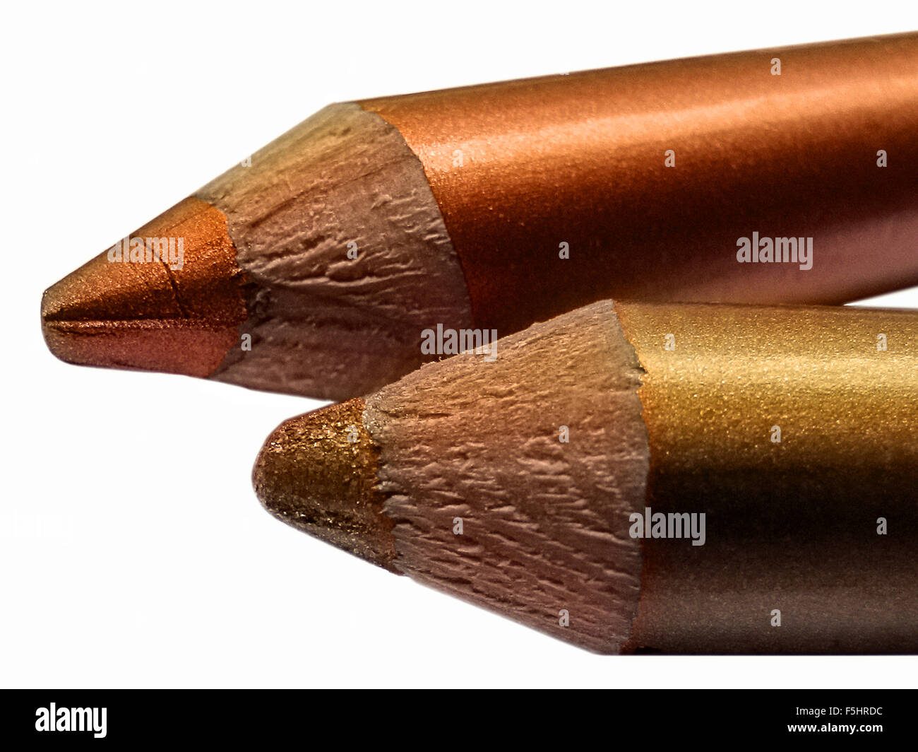 Part of metallic cream eyeshadow pencils orange and brown gold - Stock Image