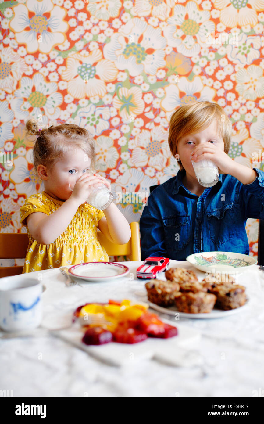 Sweden, Boy (10-11) and girl (2-3) drinking milk - Stock Image