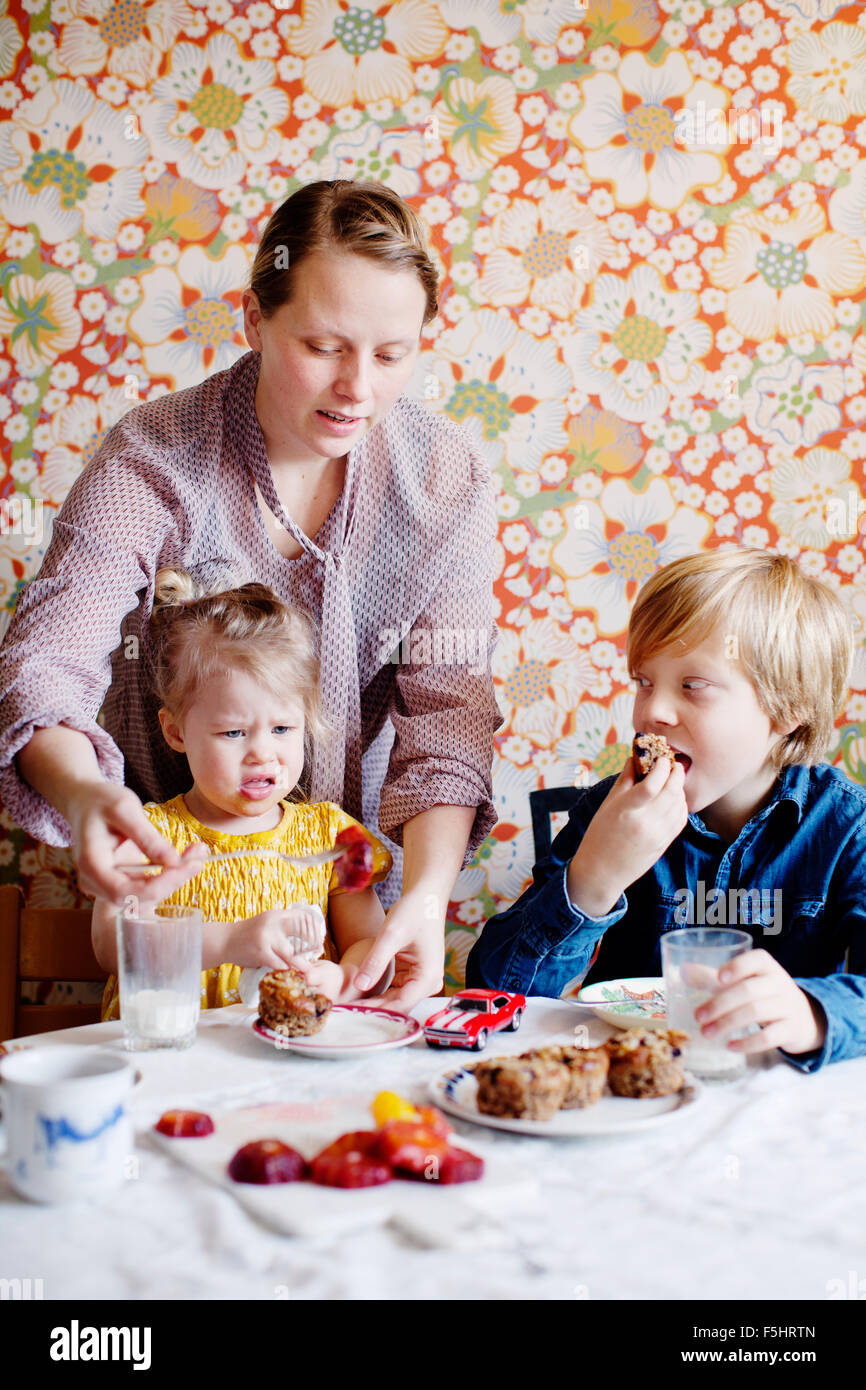 Sweden, Boy (10-11) and girl (2-3) eating cake - Stock Image