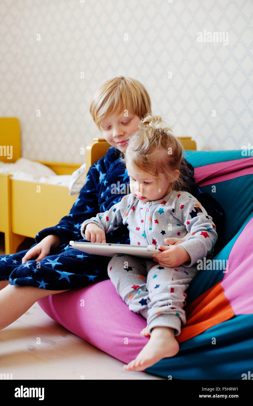 Sweden, Boy (10-11) and girl (2-3) using tablet Stock Photo