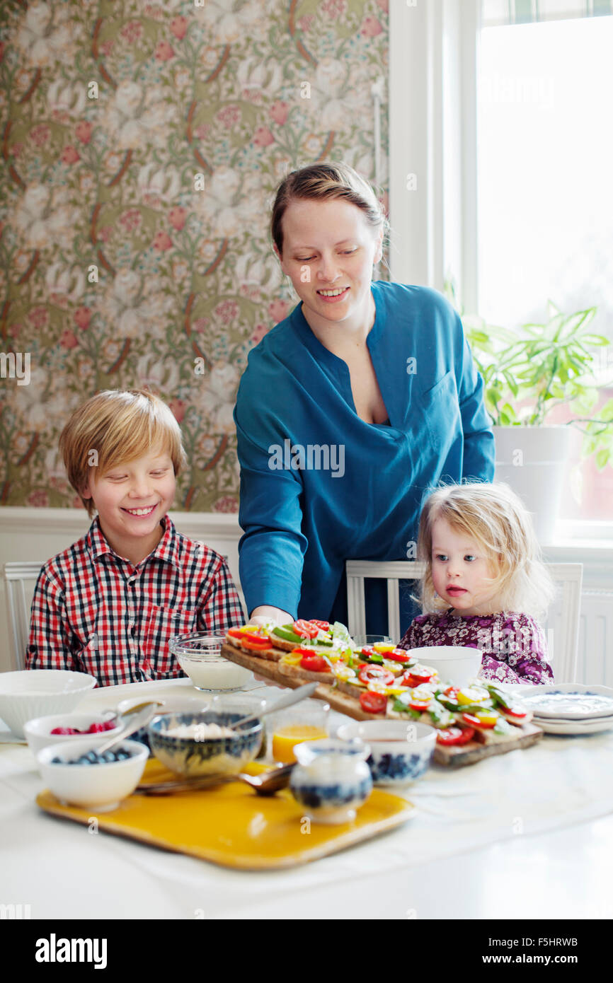 Sweden, Mother with two children (2-3, 10-11) eating breakfast Stock Photo