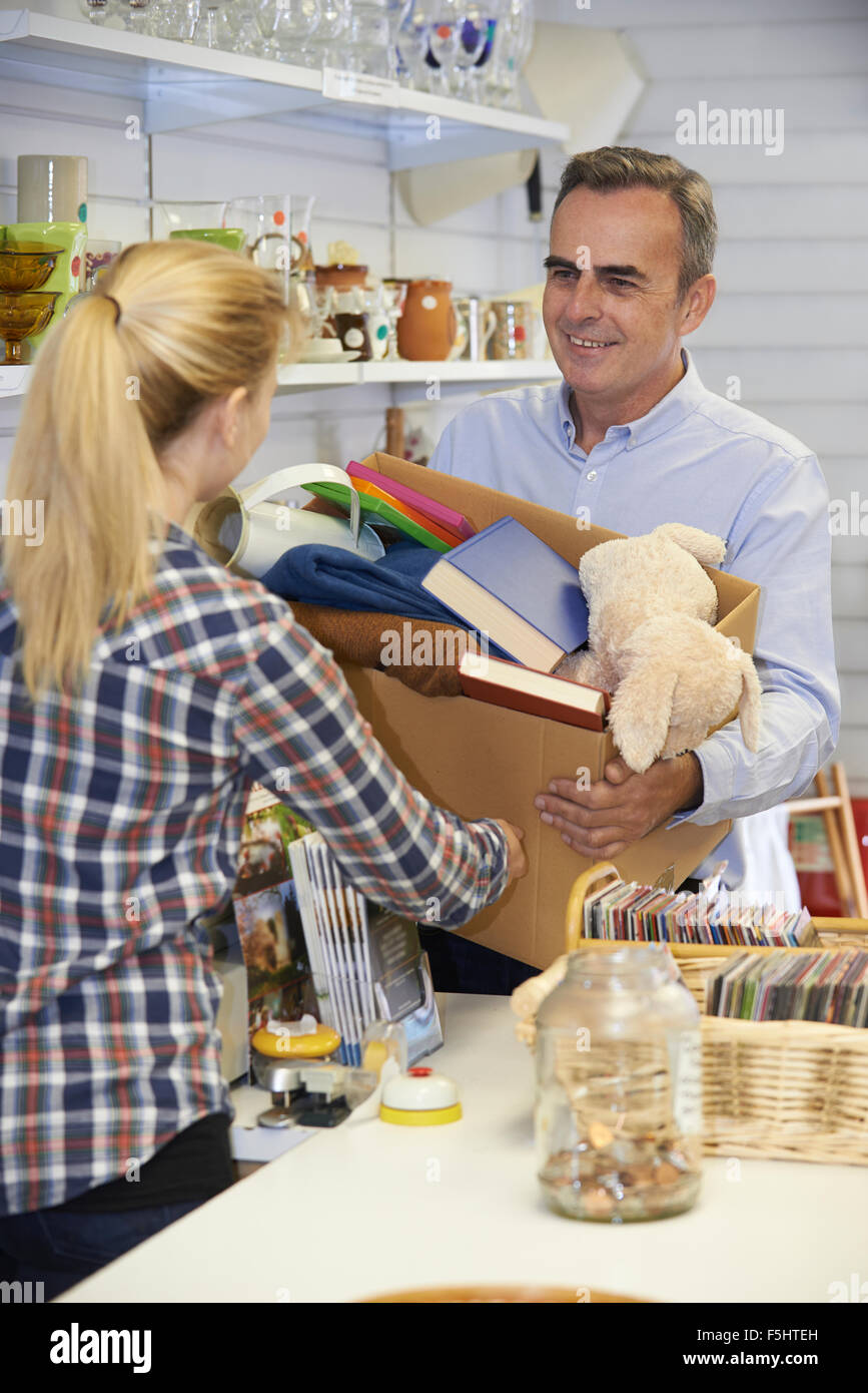 Man Donating Unwanted Items To Charity Shop - Stock Image
