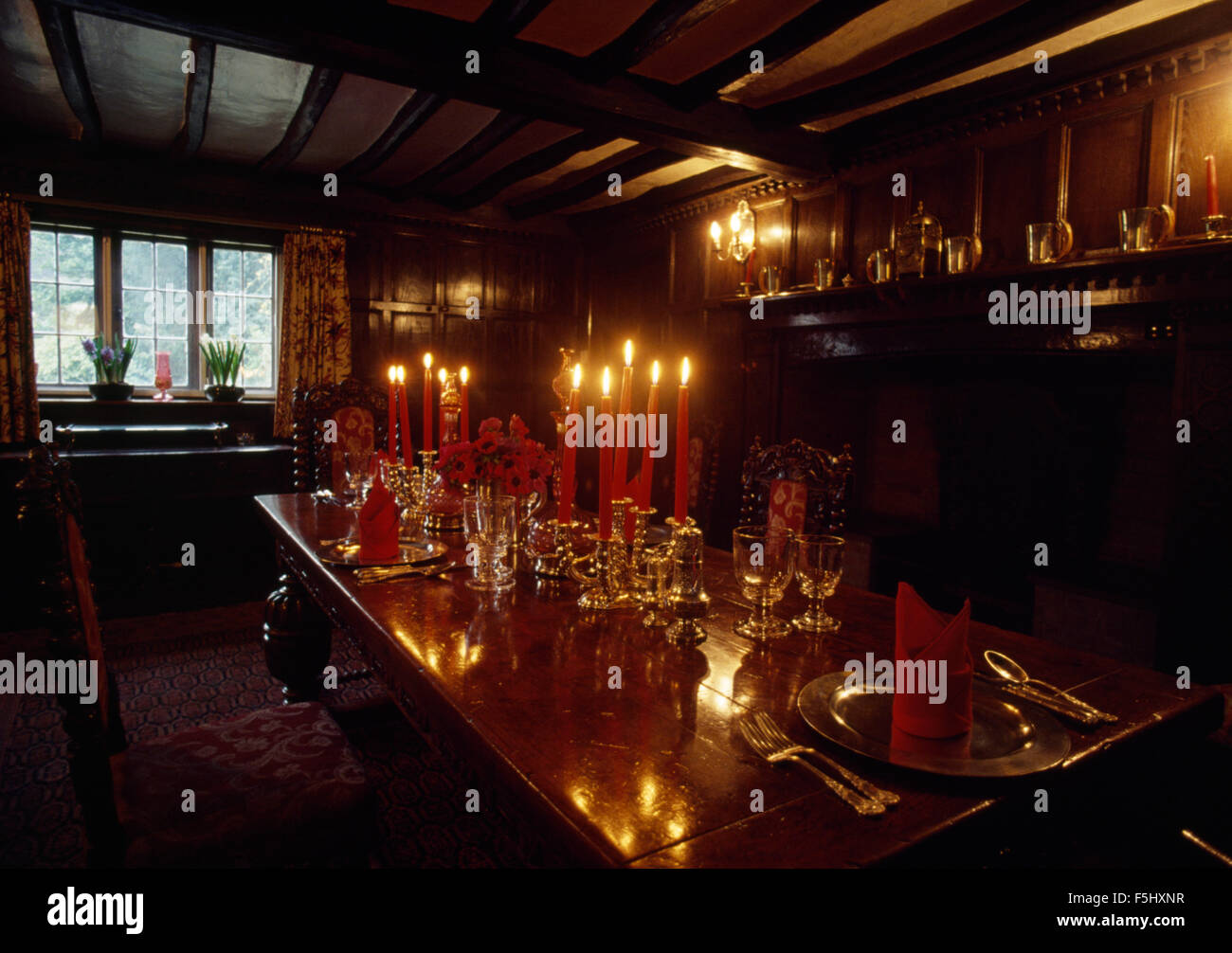 Glassware and lighted candles on table in Tudor style dining room - Stock Image