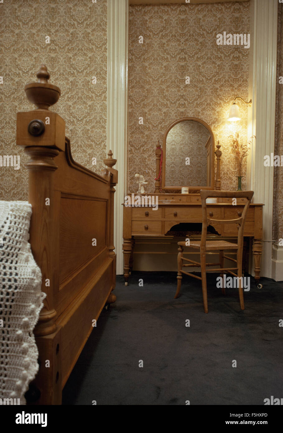 Muted wallpaper and old fashioned dressing table in seventies bedroom - Stock Image