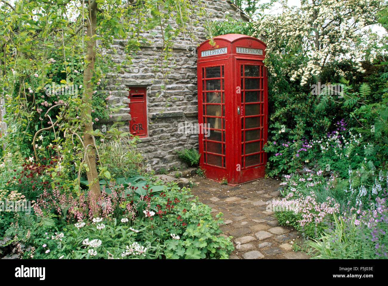 Vintage post box on stone wall in garden with a red vintage telephone box Stock Photo