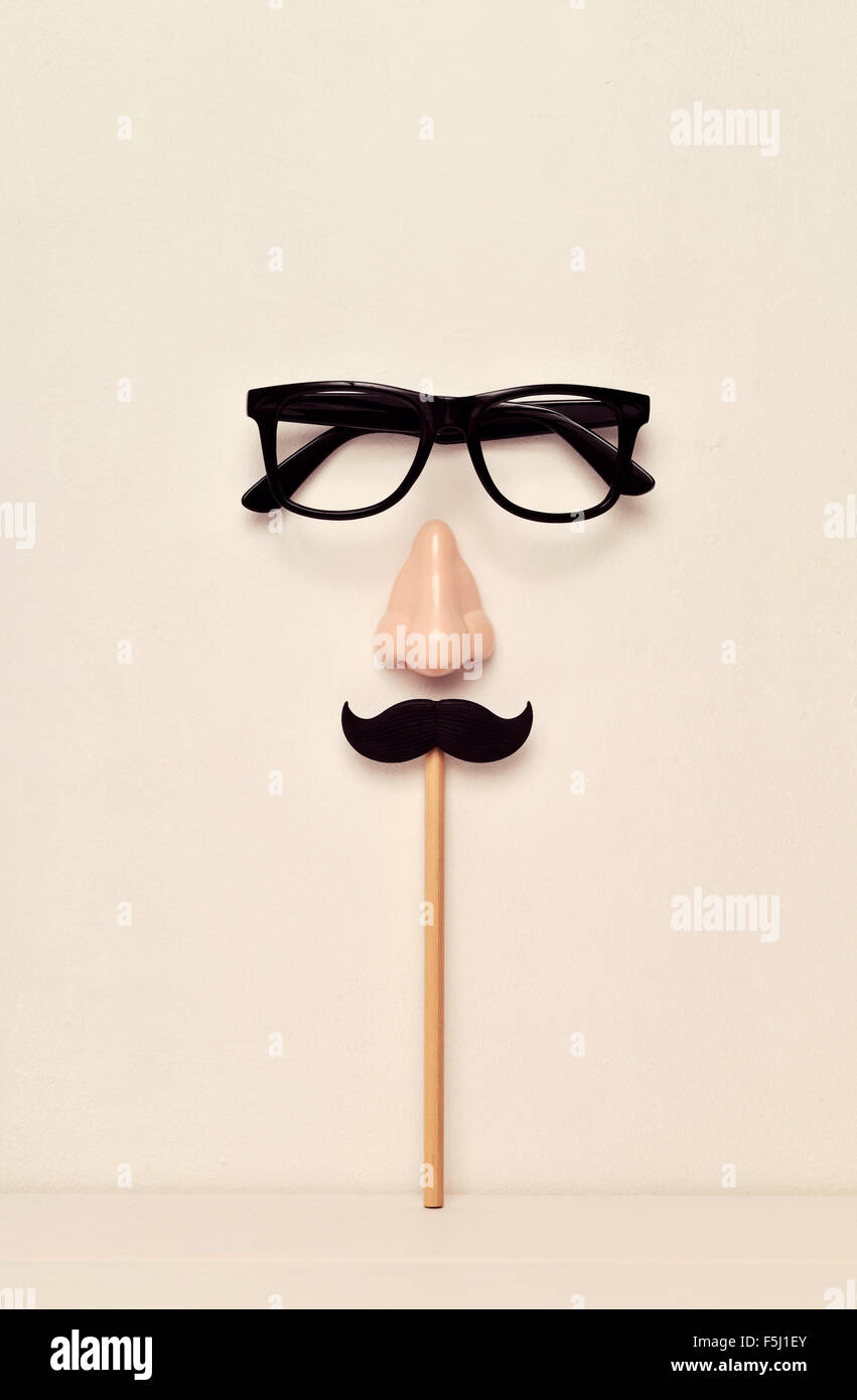 eyeglasses, nose and mustache, depicting a man face, on a beige background - Stock Image