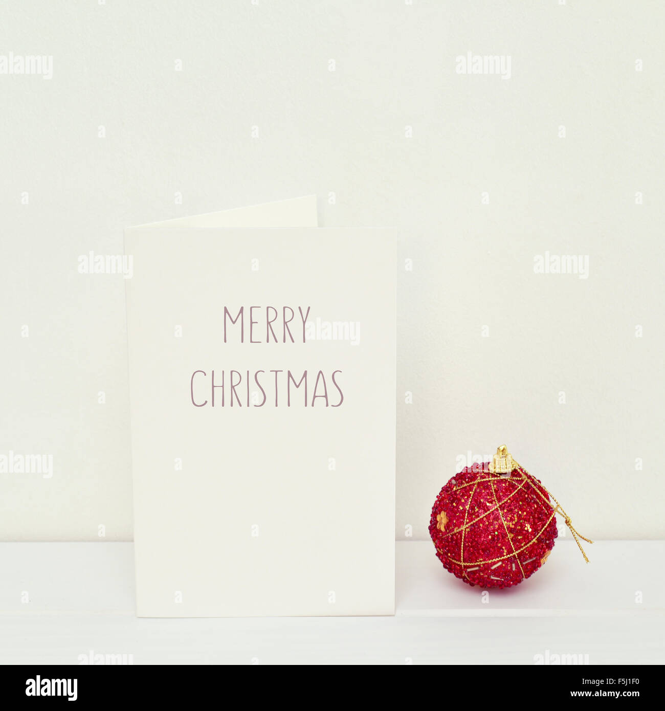 a red Christmas ball and a white greeting card with the text merry christmas in a white scene - Stock Image