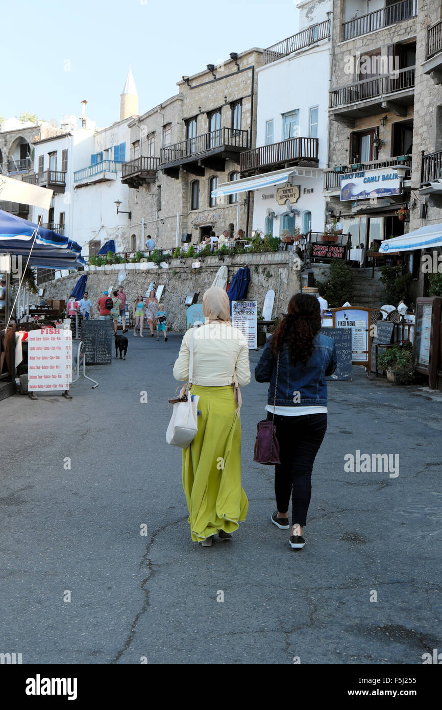 Rear view of two women friends walking along the harbour front in Kyrenia Girne North Cyprus  KATHY DEWITT - Stock Image
