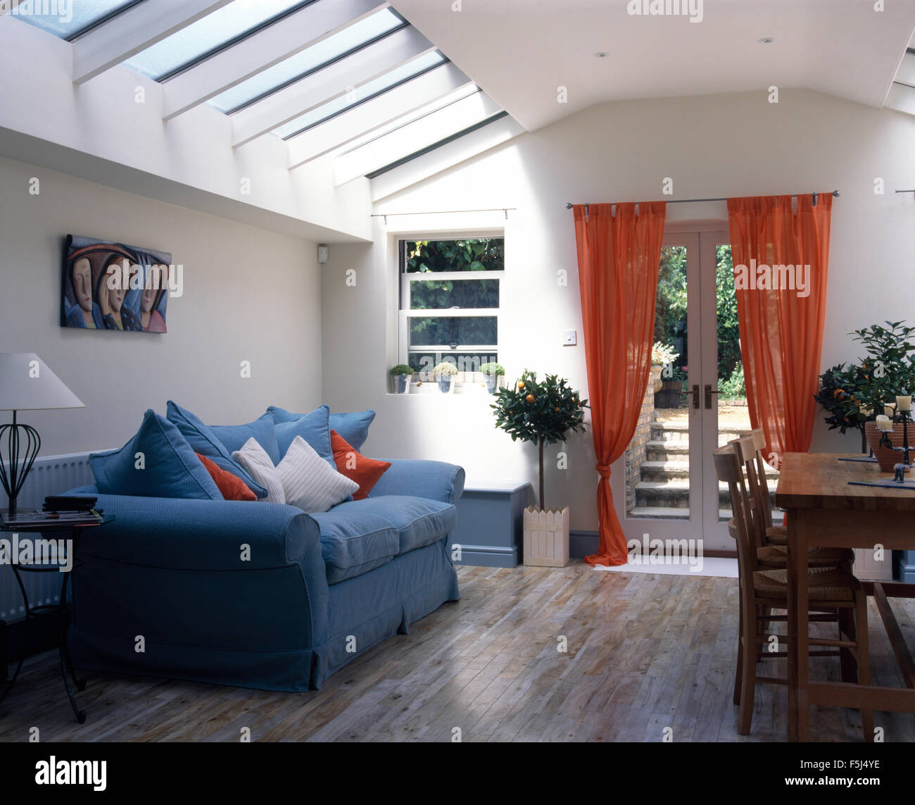 Blue sofa and orange voile drapes in living and dining room extension with wooden flooring Stock Photo