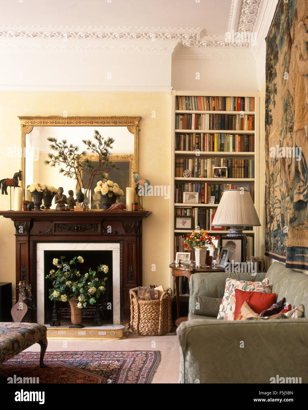 Gilt Mirror Above Fireplace In A Very Traditional Living Room With Bookshelves And Gray Sofa