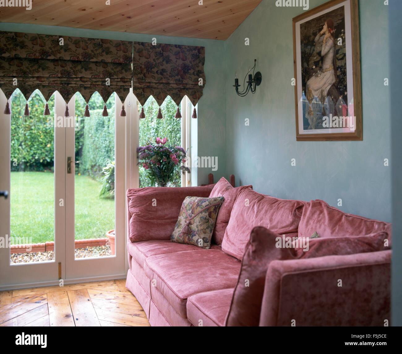pink velvet sofa in a blue nineties living room with a tasseled roman blind on glass - Pink Velvet Sofa