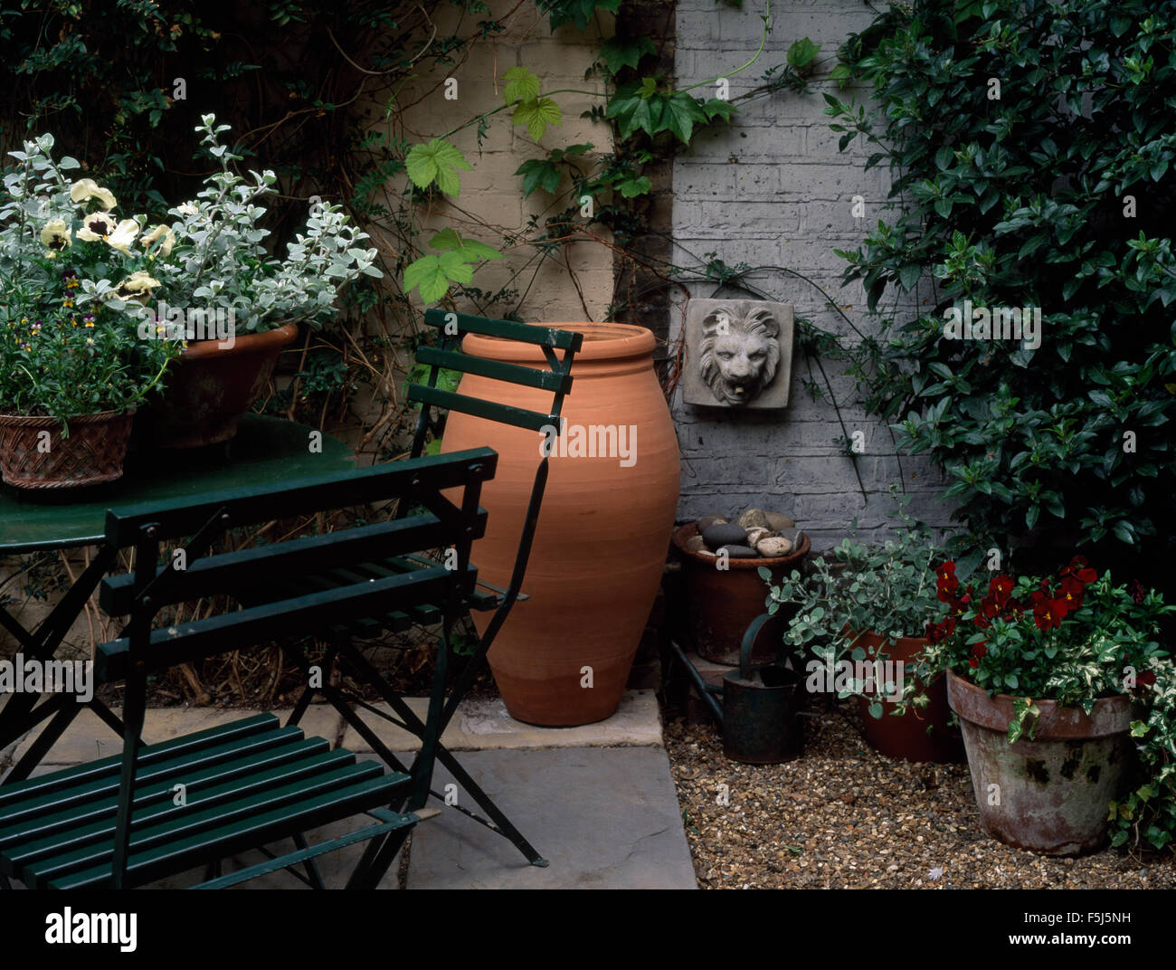 Picture of: Foliage Plants In Pots On Small Table With Slatted Chairs On A Town Stock Photo Alamy