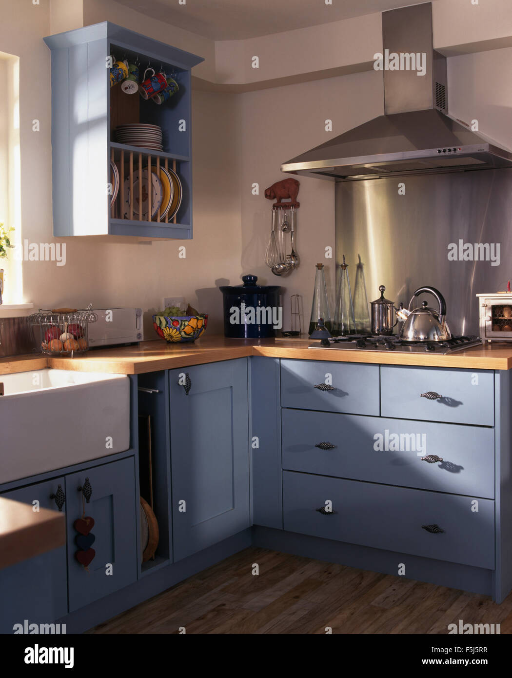 Stainless Steel Extractor And Splash Back Above The Hob In A Kitchen With  Pale Blue Fitted Units