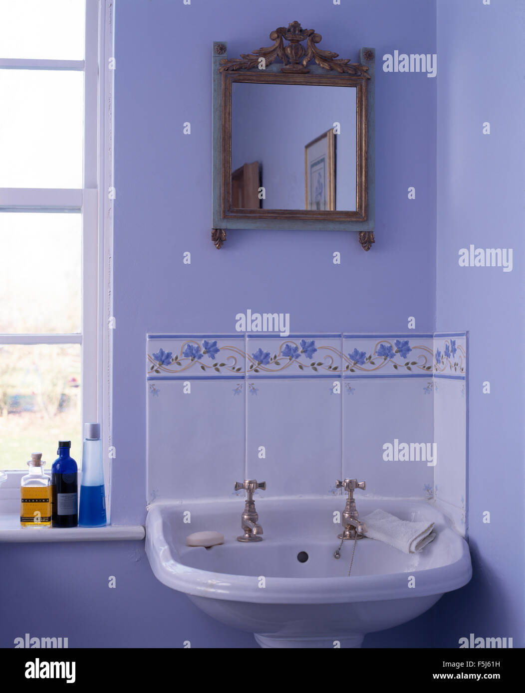 Small Antique Gilt Mirror Above Washbasin In A Blue Bathroom Stock