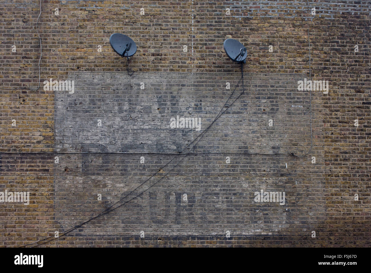 Old century advertising for a former dentist business fading on a brick wall in east Dulwich, south London. - Stock Image