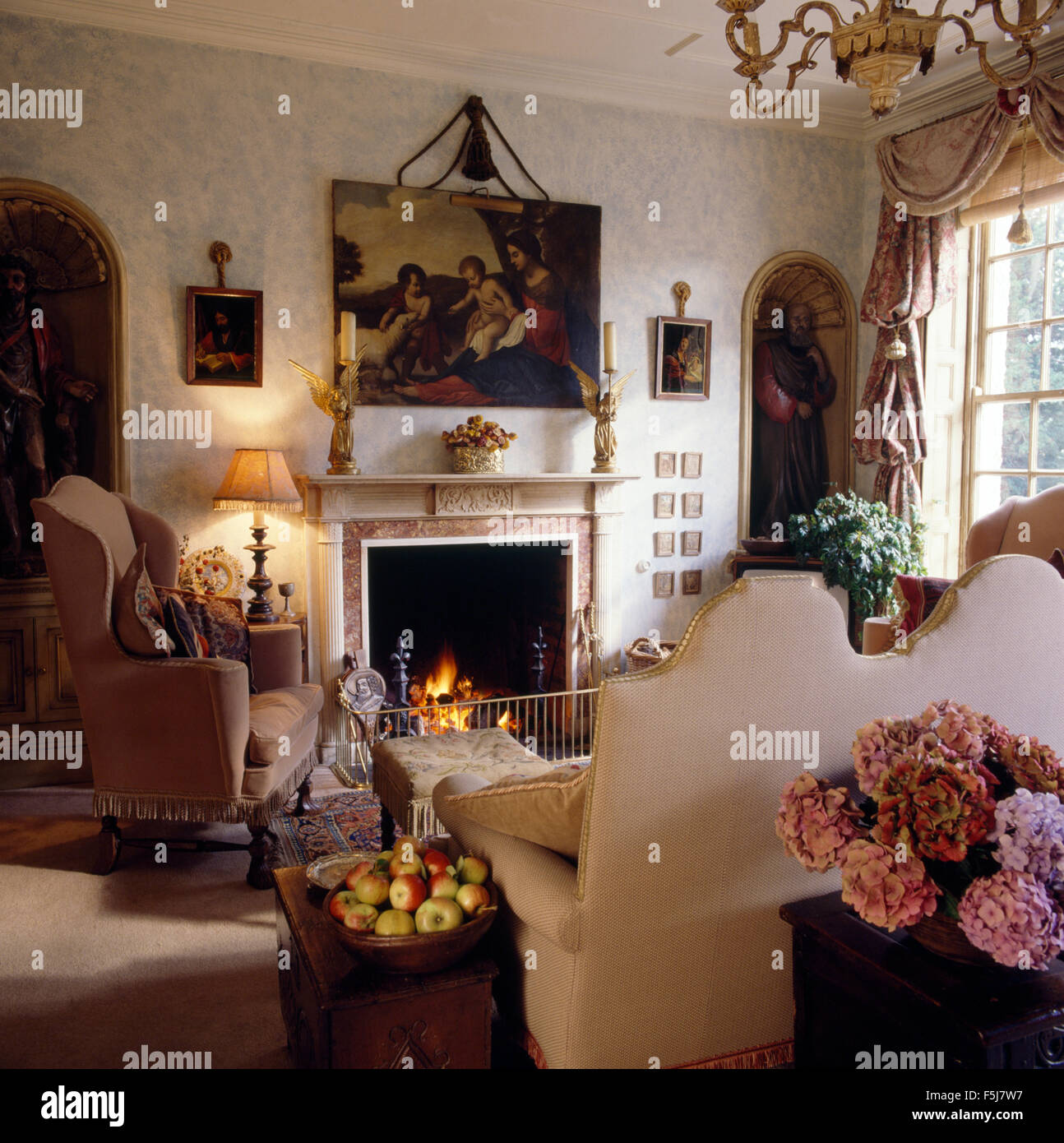 Painting Above Fireplace With Lighted Fire In Opulent Eighties Living Room  With A Wing Chair And A Cream Camel Back Sofa